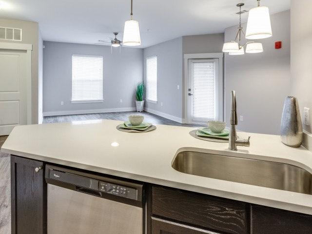 Enjoy Our Granite Look Countertops, With View of White Counters, Deep Sink, and Breakfast Bar at Cottonwood Reserve Apartments