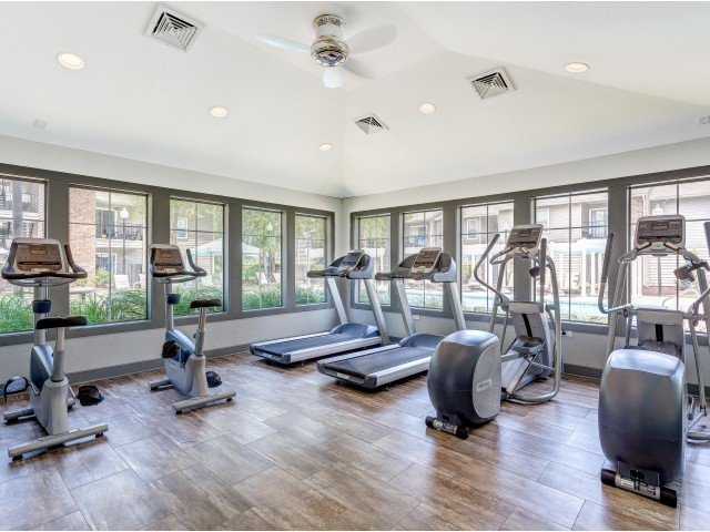 Enjoy Our Fitness Center, With View of Cardio Machines, Wood Floors, and View of Windows at 1070 Main Apartments