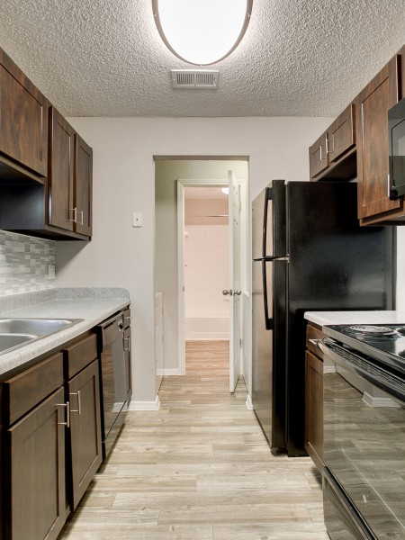 View of the Kitchen at The Arbors of Las Colinas Apartments, Showing Plank Wood Flooring and Gas Appliances