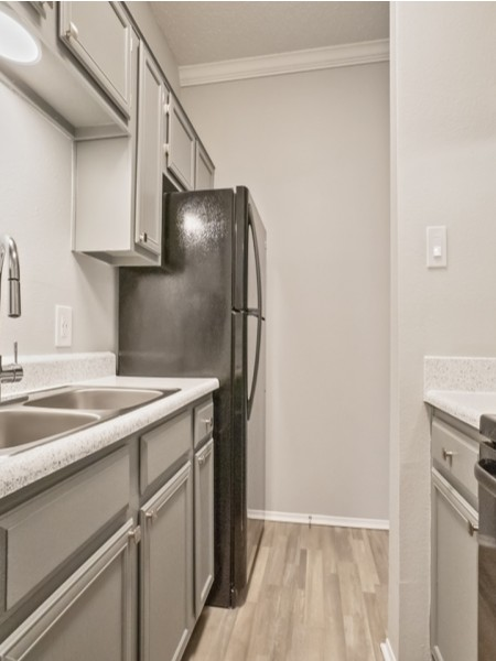 View of the Renovated Apartment Interior at The Oaks of North Dallas Apartments, Showing Kitchen with Plank Wood Flooring and Appliances