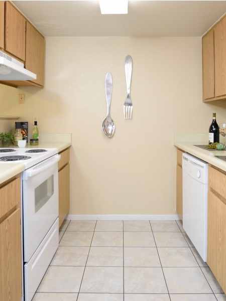 View of the Kitchen at Camelot Apartments, Showing Gas Appliances, Tile Flooring, Cabinets, Countertops, and Sink