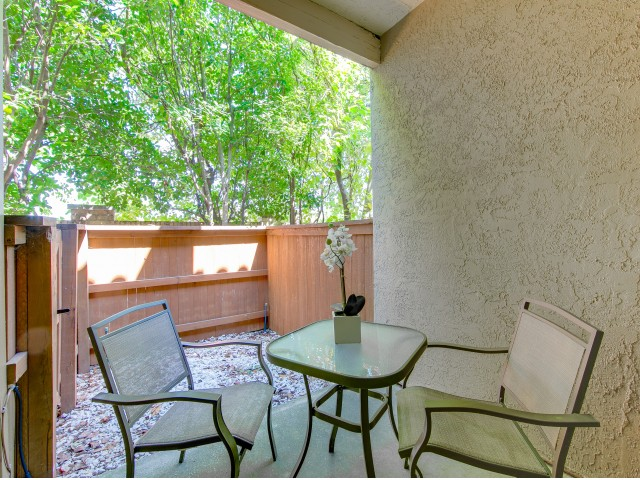 Enjoy Our Private Patios and Balconies, With View of Table With Two Chairs on a Sunny Day at Spring Pointe Apartments