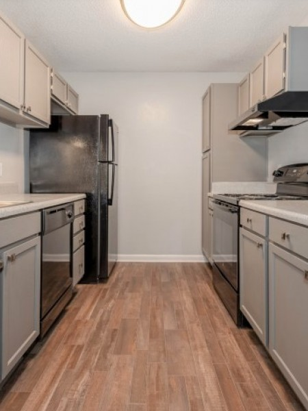 View of the Renovated Apartment Kitchen at Plantations at Haywood Apartments, Showing Kitchen with Gas Appliances and Plank Wood Flooring
