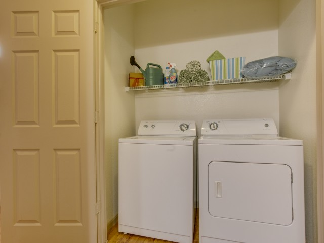 Enjoy Our Full Size Washer and Dryer Included, With View of Laundry Room and Plank Flooring at Retreat at Stafford Apartments