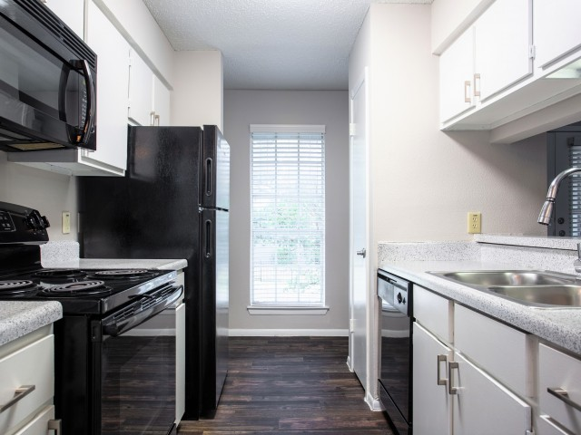 View of Renovated Apartment Interior, Showing Kitchen, Electric Stove, Double Sink, Cabinets, Countertops, and Plank Flooring at Blue Swan Apartments