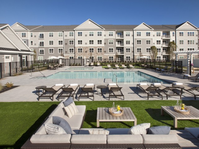 Enjoy Our Pool Views, With View of Loungers, Outdoor Couches, and Apartment Building in Background at Parc Westborough Apartments