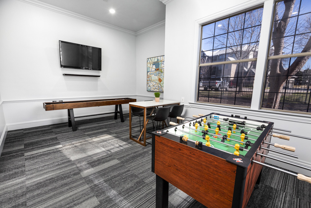 View of Game Room, Showing Foozeball Table, Shuffleboard, Flat Screen TV and Large Window at Stonebriar of Frisco Apartments