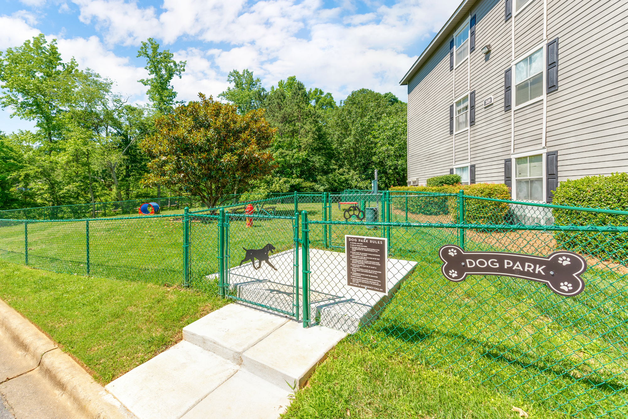 Enjoy Our Pet Park, With View of Fenced in Dog Agility Course and Grassy Area at Waterford Creek Apartments