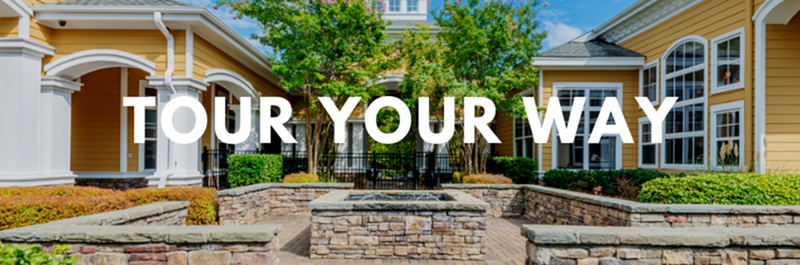 Tour Your Way - View of Building Exterior, Showing Brick-Paved Walkway, Fenced-In Area, and Landscaping at Cottonwood Reserve Apartments