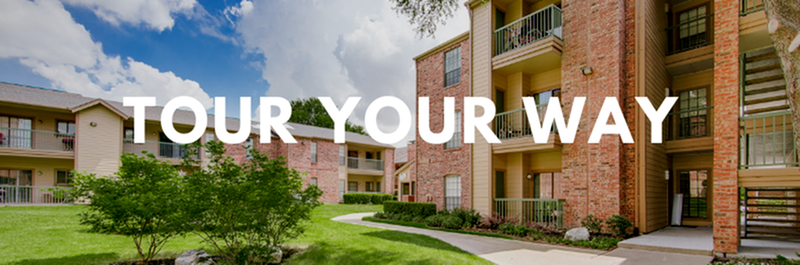 Tour Your Way - View of Building Exterior, Showing Landscaping, Parking Lot, and Private Patios and Balconies at Oaks of North Dallas Apartments