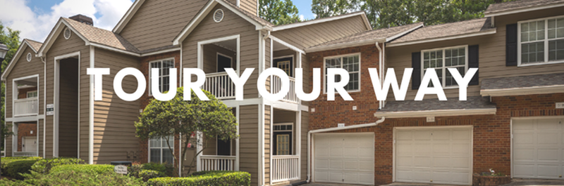 Tour Your Way - View of Building Exterior, Showing Garages, Private Patios and Balconies, and Landscaping at Retreat at Peachtree City Apartments