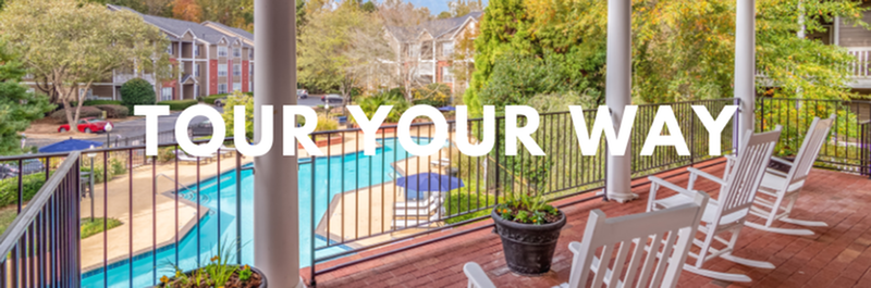 Tour Your Way - View of Balcony, Showing Fenced-In Pool, Loungers, and Apartment Buildings in Background at River Park Apartments