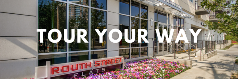 Tour Your Way - View of Building Exterior, Showing Leasing Center Entrance, Signage, and Flower Bed at Routh Street Flats Apartments