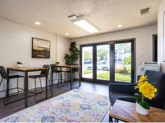 View of Wi-Fi Café, Showing French Doors, Seating Area, High Top Tables With Charging Stations and Chairs at Solara Apartments