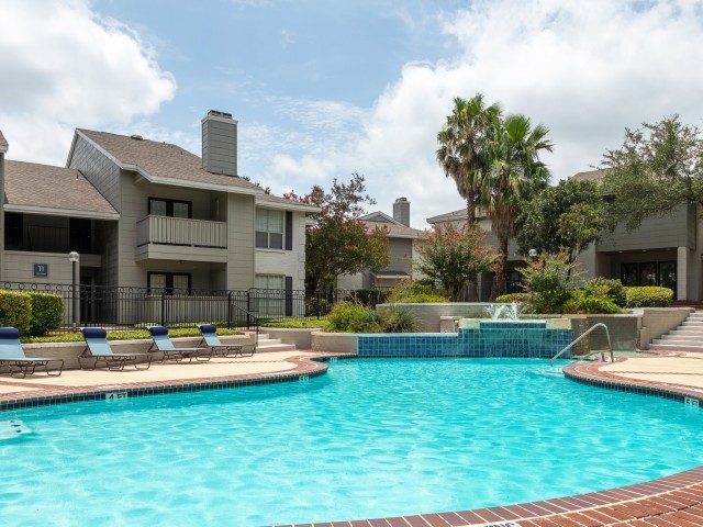 View of Phase 1 Resort-Style Pool, Showing Lounge Chairs, Sundeck, Landscaping, and Building Exteriors at Solara Apartments