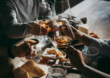 Image showing multiple people toasting with wine, cheese board, and bread. at The Fountainhead Wine and Beer Bar