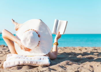 Image of a woman with large hat laying on the beach reading a book facing the ocean. at Clearwater Beach