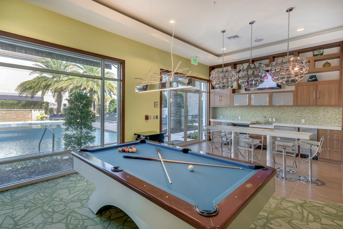 View of Resident Lounge, Showing Pool Table, Long Table, and Community Kitchen at The Marq Highland Park Apartments