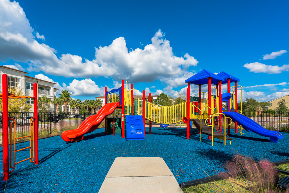 View of Playground, Showing Playground Equipment, Monkey Bars, and Slides at The Marq Highland Park Apartments