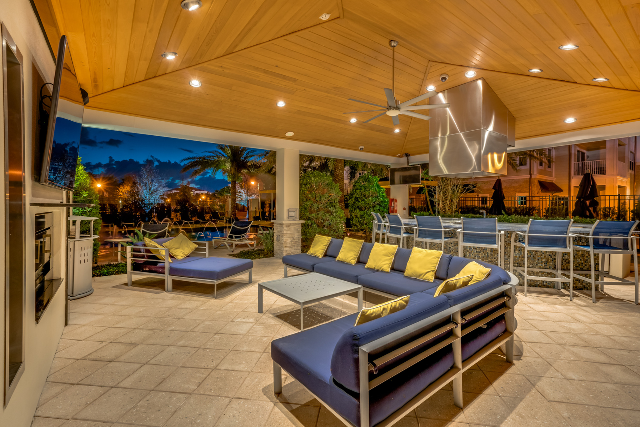 View of Grilling Lounge, Showing Pavilion Area, Outdoor Couch, TV, and Chairs in Circle Around Grill at The Marq Highland Park Apartments