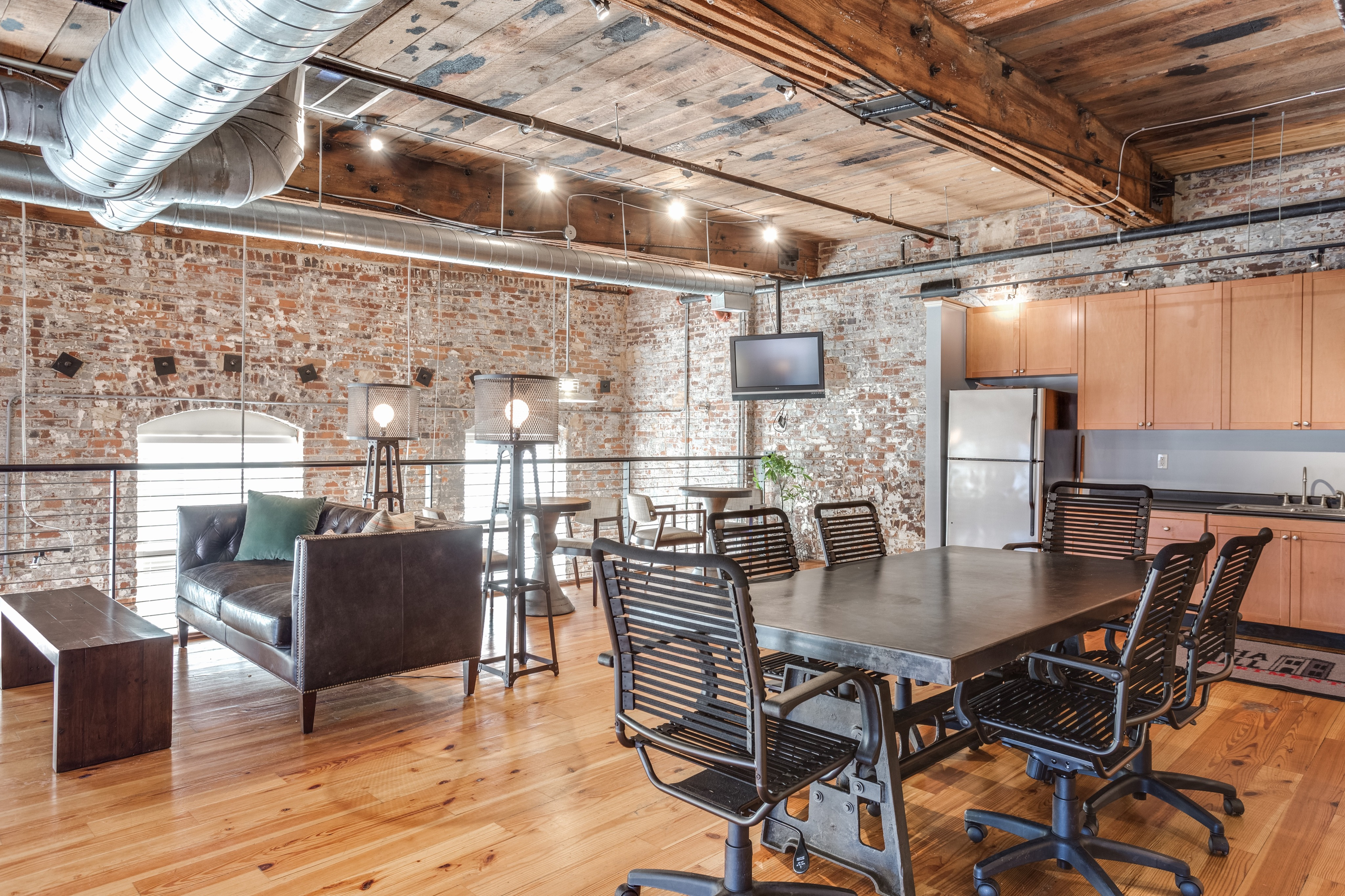 View of Business Center, Showing Meeting Table, Chairs, Sitting Areas, and Community Kitchen at Alpha Mill Apartments