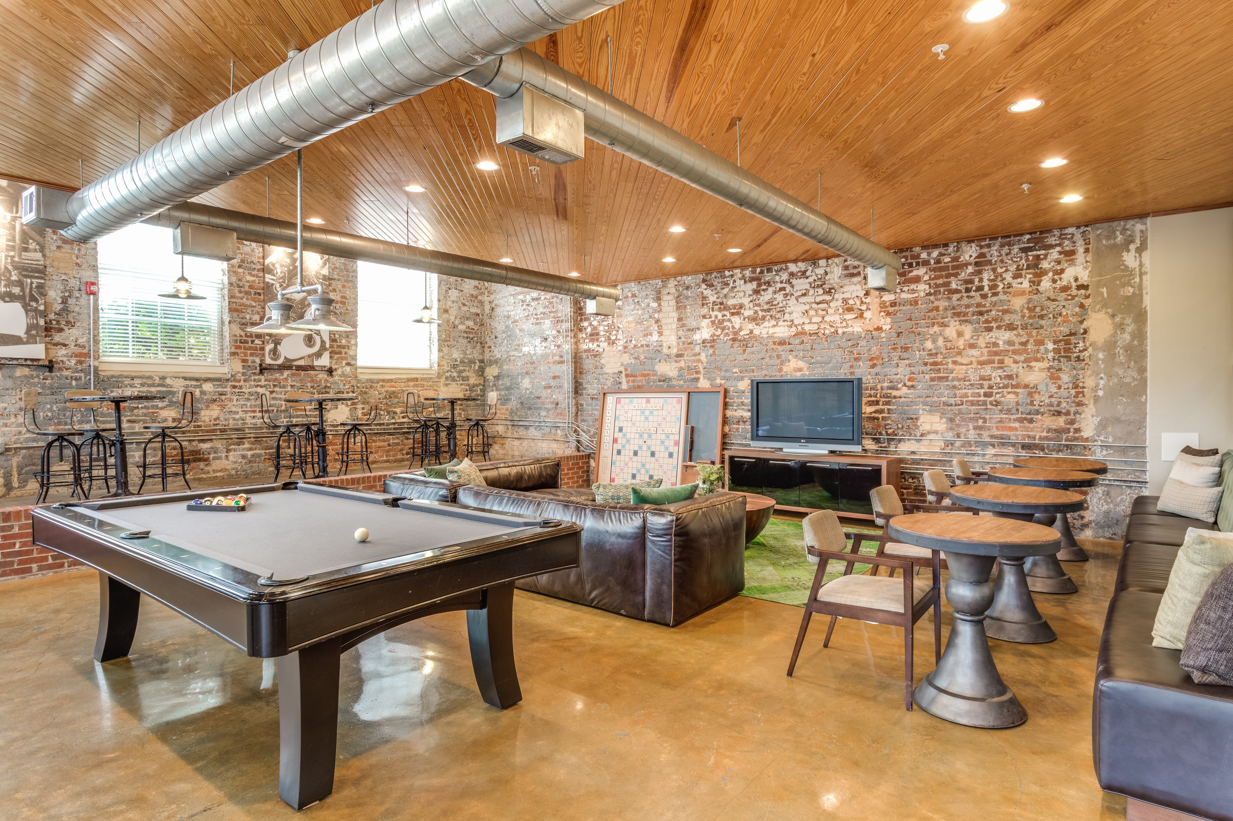 View of Resident Lounge, Showing Pool Table, Sitting Areas, TV, and Mill Architecture at Alpha Mill Apartments