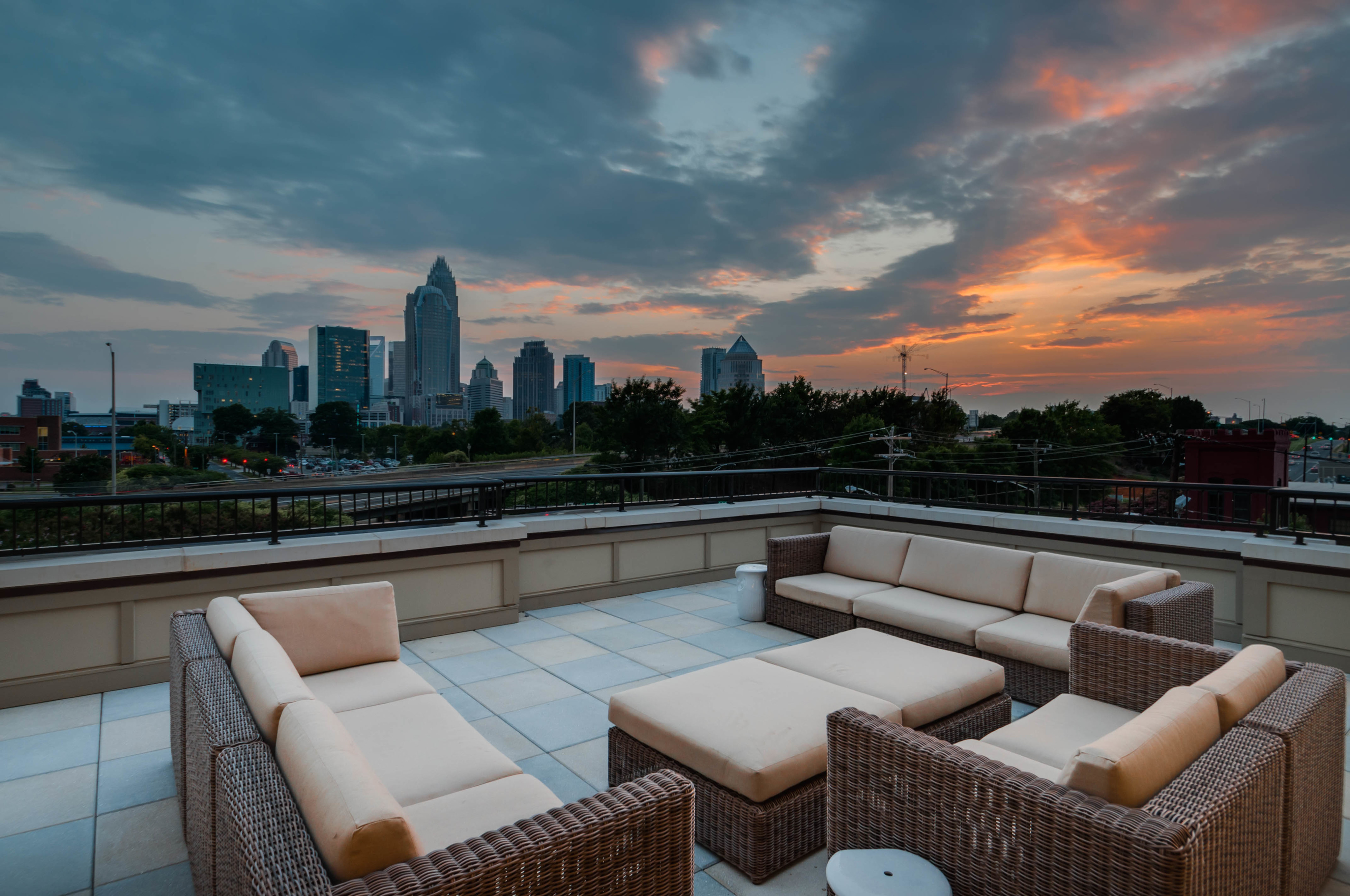View of Rooftop Lounge, Showing Outdoor Couches, Sky at Sunset, and Views of Uptown Charlotte at Alpha Mill Apartments