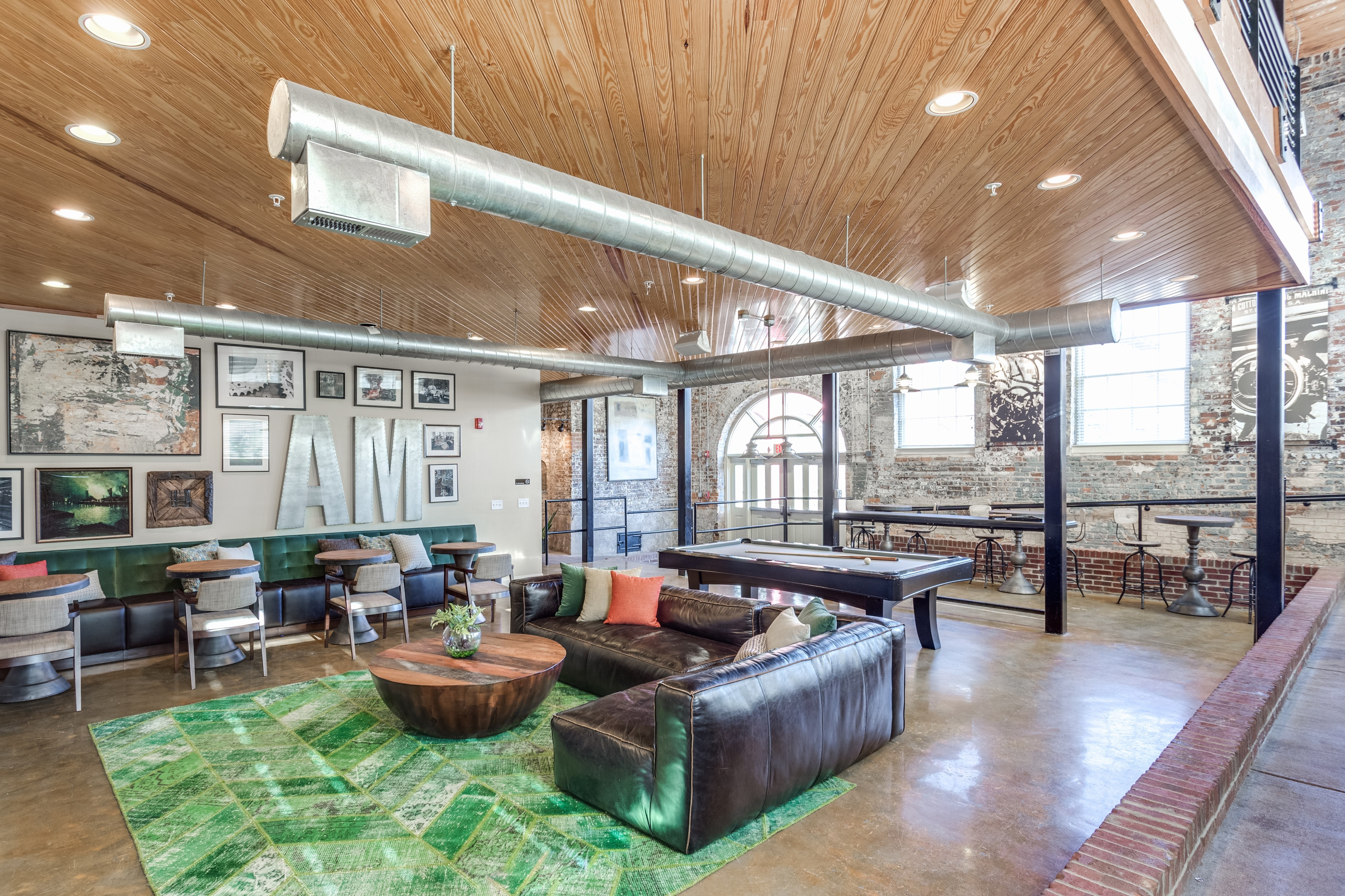 View of Resident Lounge, Showing Seating Area, Pool Table, and Mill Architecture at Alpha Mill Apartments