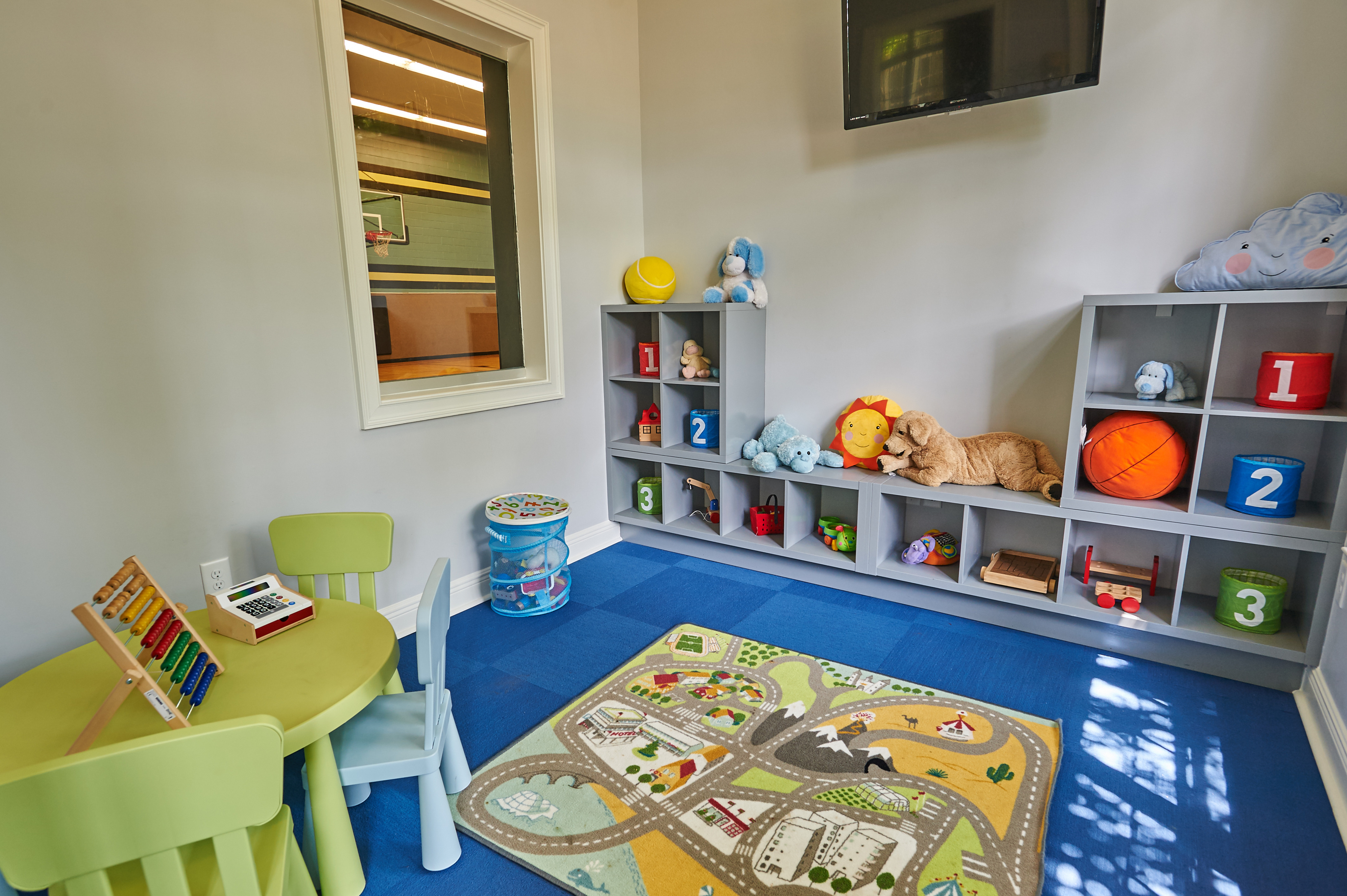 View of Children\'s Activity Room, Showing Table With Chairs, Games, Cubbies, and Window Into Sport Court at Cottonwood Reserve Apartments