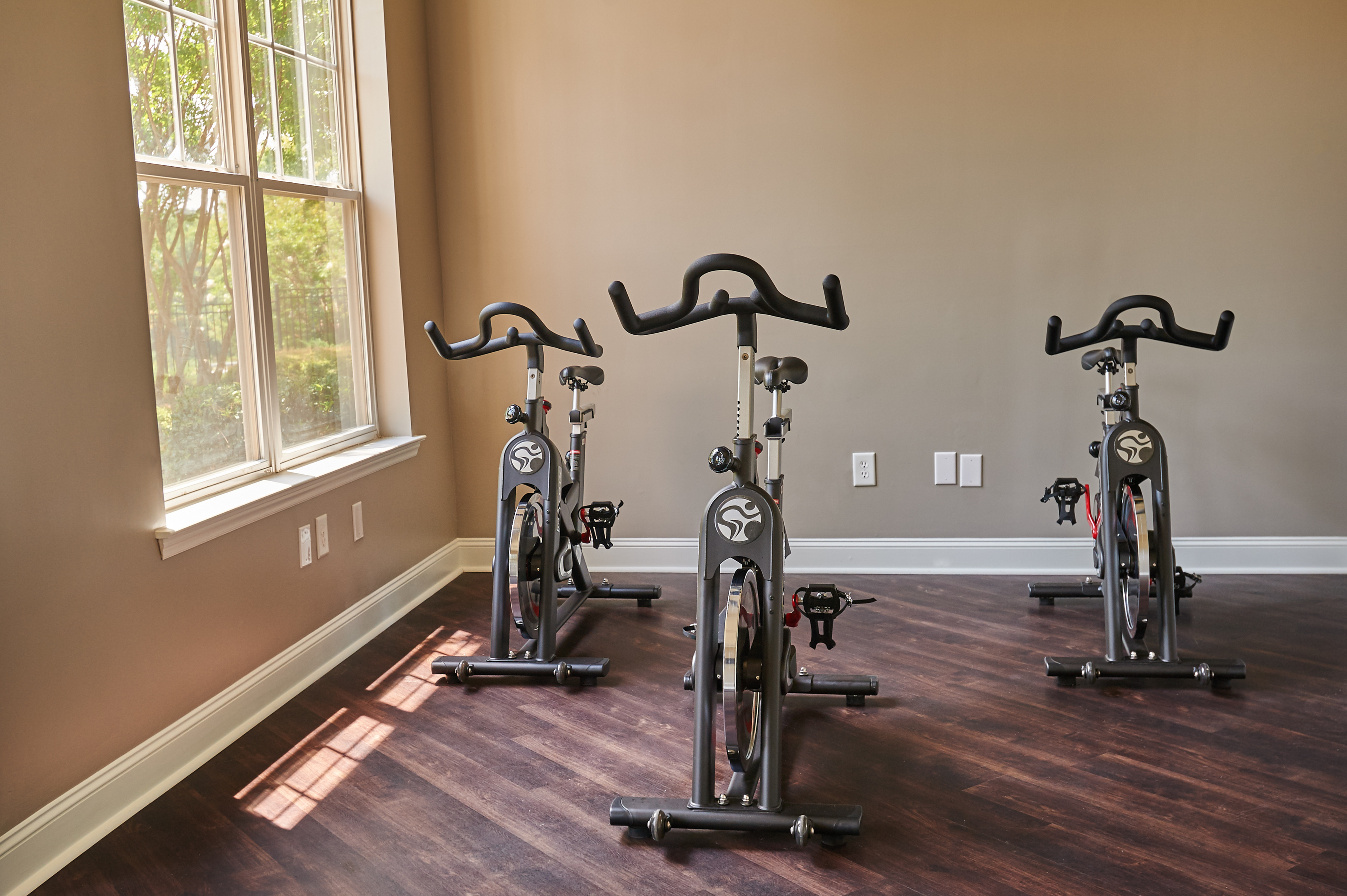 View of Spin and Yoga Studio, Showing Spin Bikes, Plank Flooring, and Window at Cottonwood Reserve Apartments