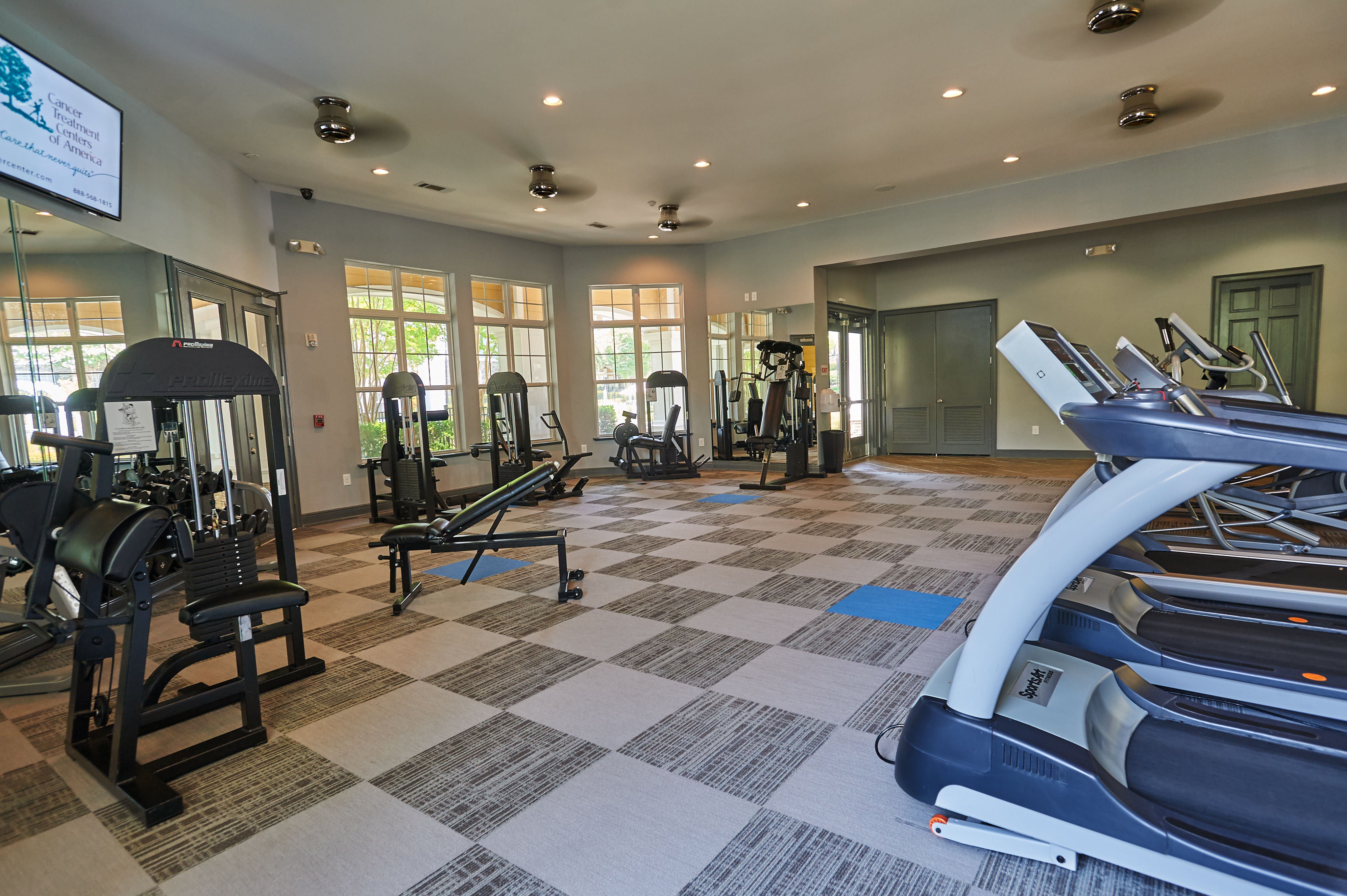 View of Fitness Center, Showing Cardio Equipment, Free Weights, and Weight Benches at Cottonwood Reserve Apartments