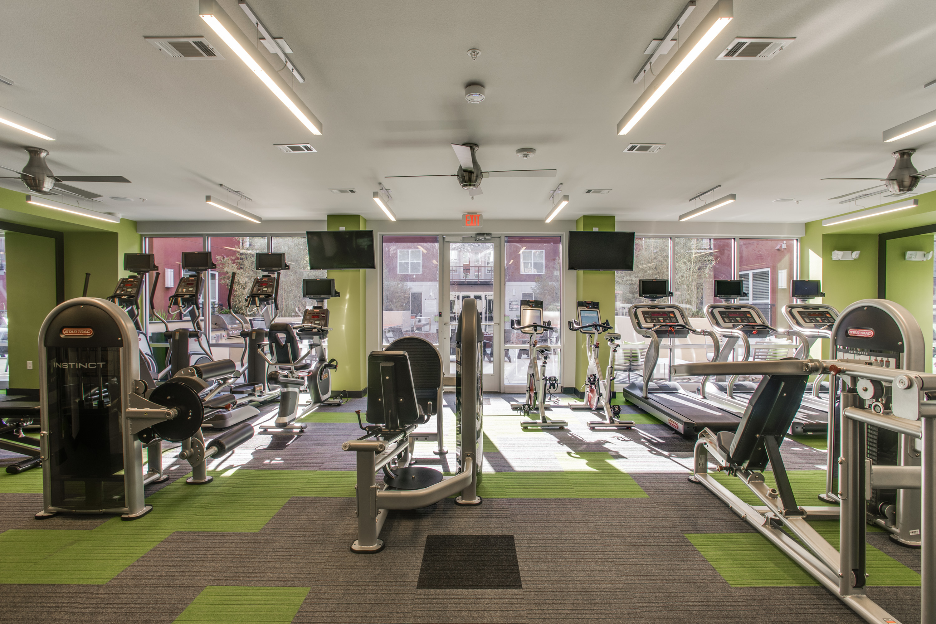 View of Fitness Center, Showing Cardio Machines, Cable Machines, and TVs at Routh Street Flats Apartments