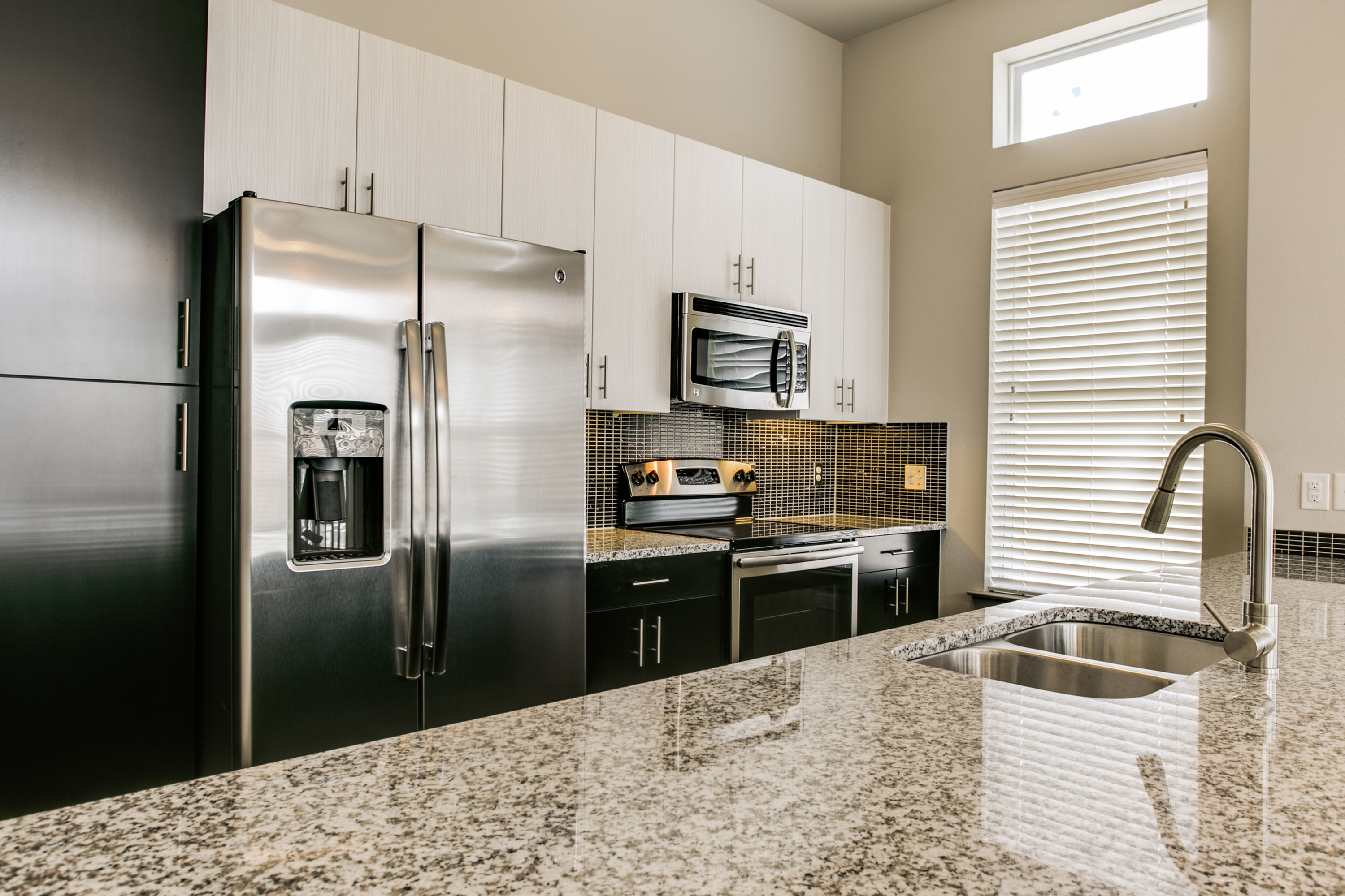 View of Kitchen, Showing Granite Counter Top and Stainless Steel Appliances at Routh Street Flats Apartments