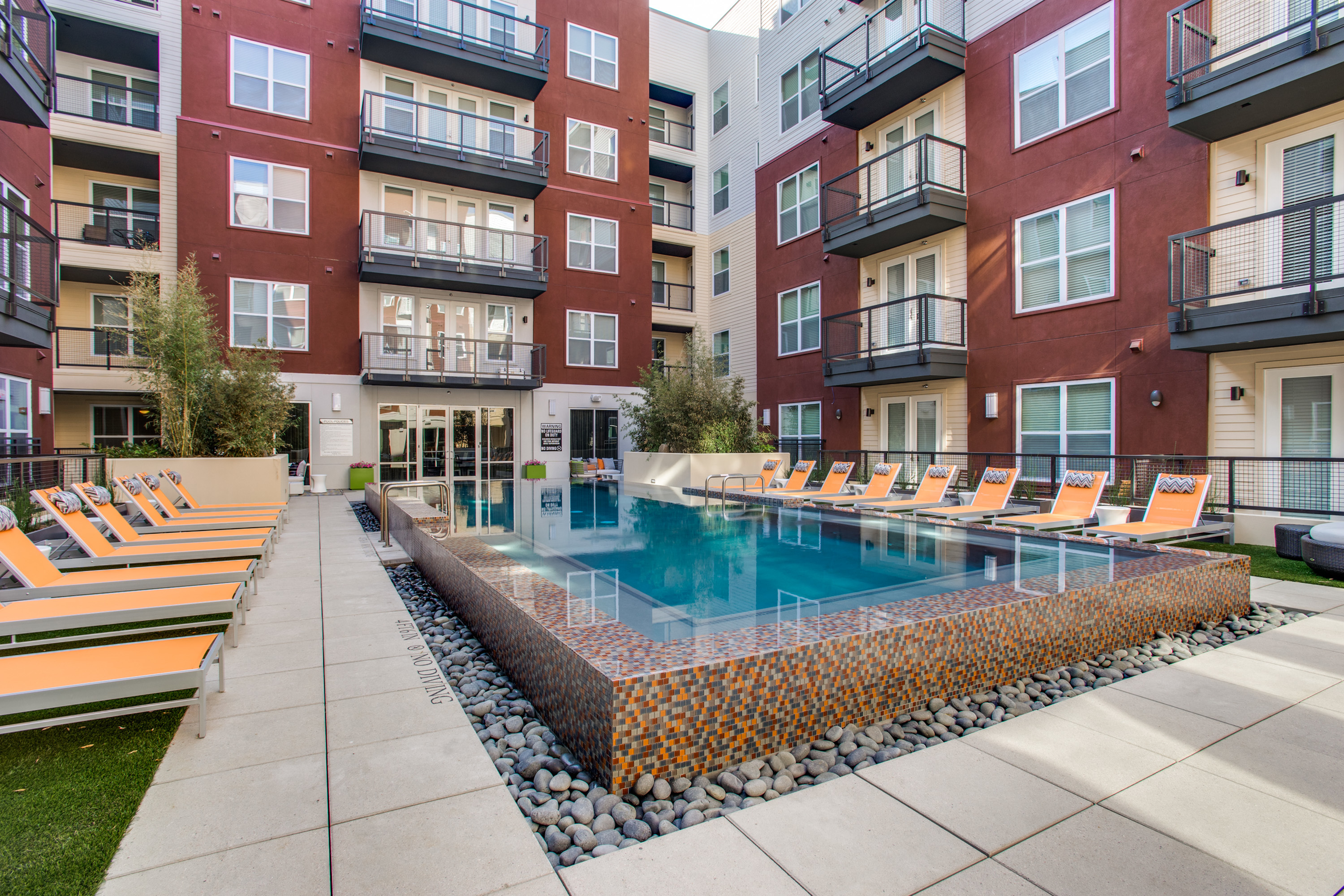 View of Pool Area, Showing Infinity-Edge Pool, Loungers, Patios, and Balconies at Routh Street Flats Apartments