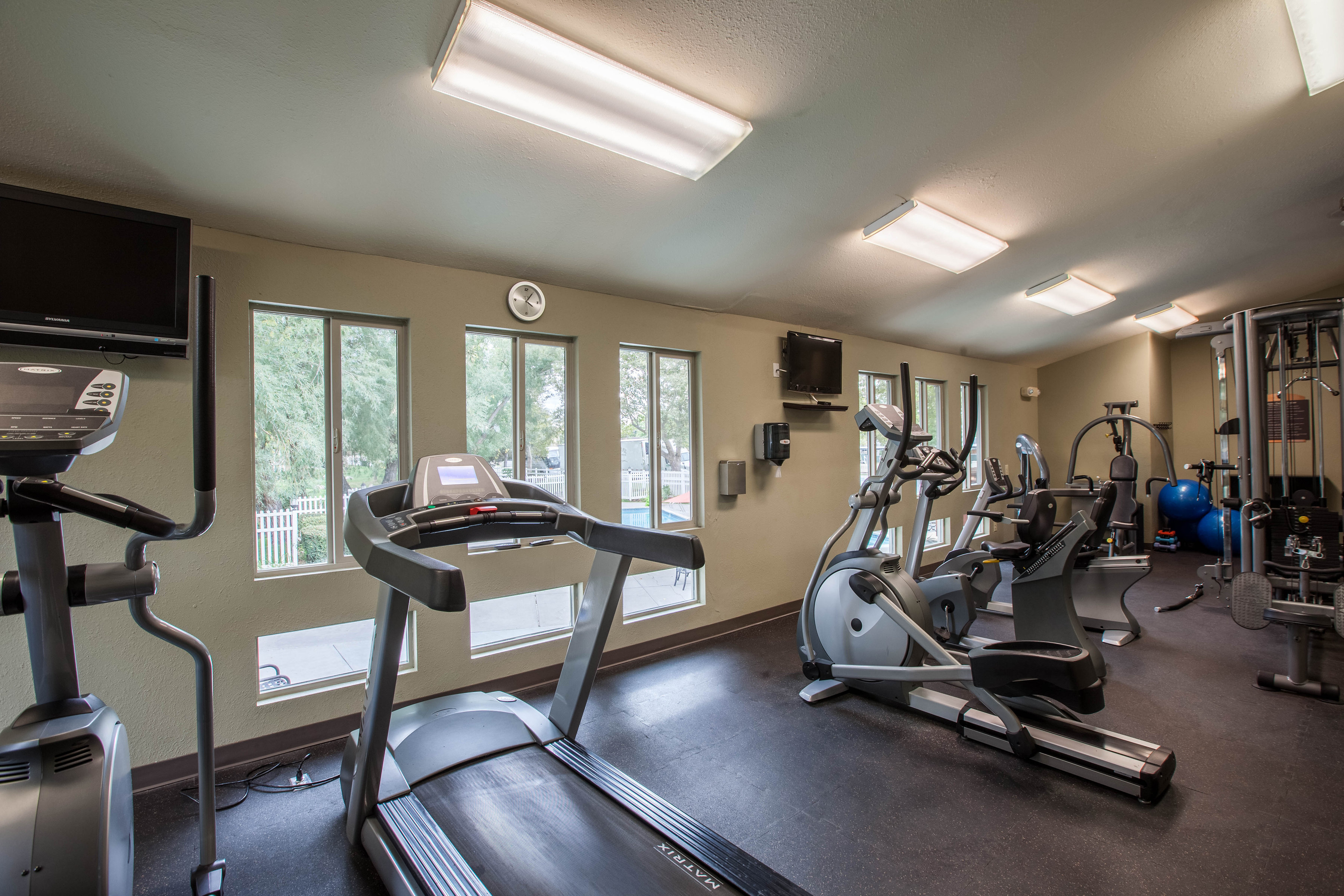 View of Fitness Center, Showing Cardio Machines, Cable Machines, and TVs at Fox Point in Old Farm Apartments