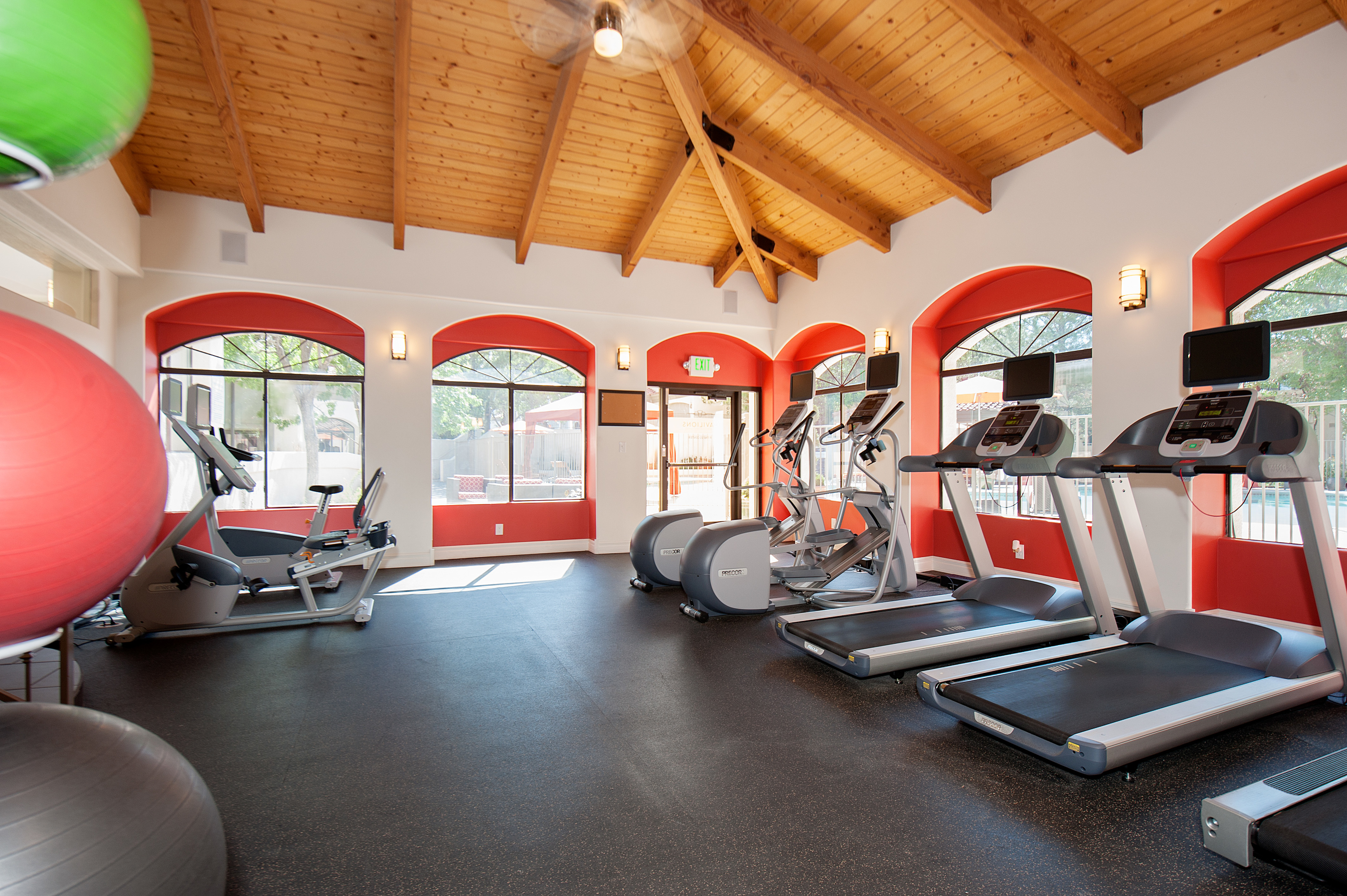 View of Fitness Center, Showing Cardio Equipment, Stability Balls, Ceiling Fan, and Wall of Windows at Pavilions Apartments