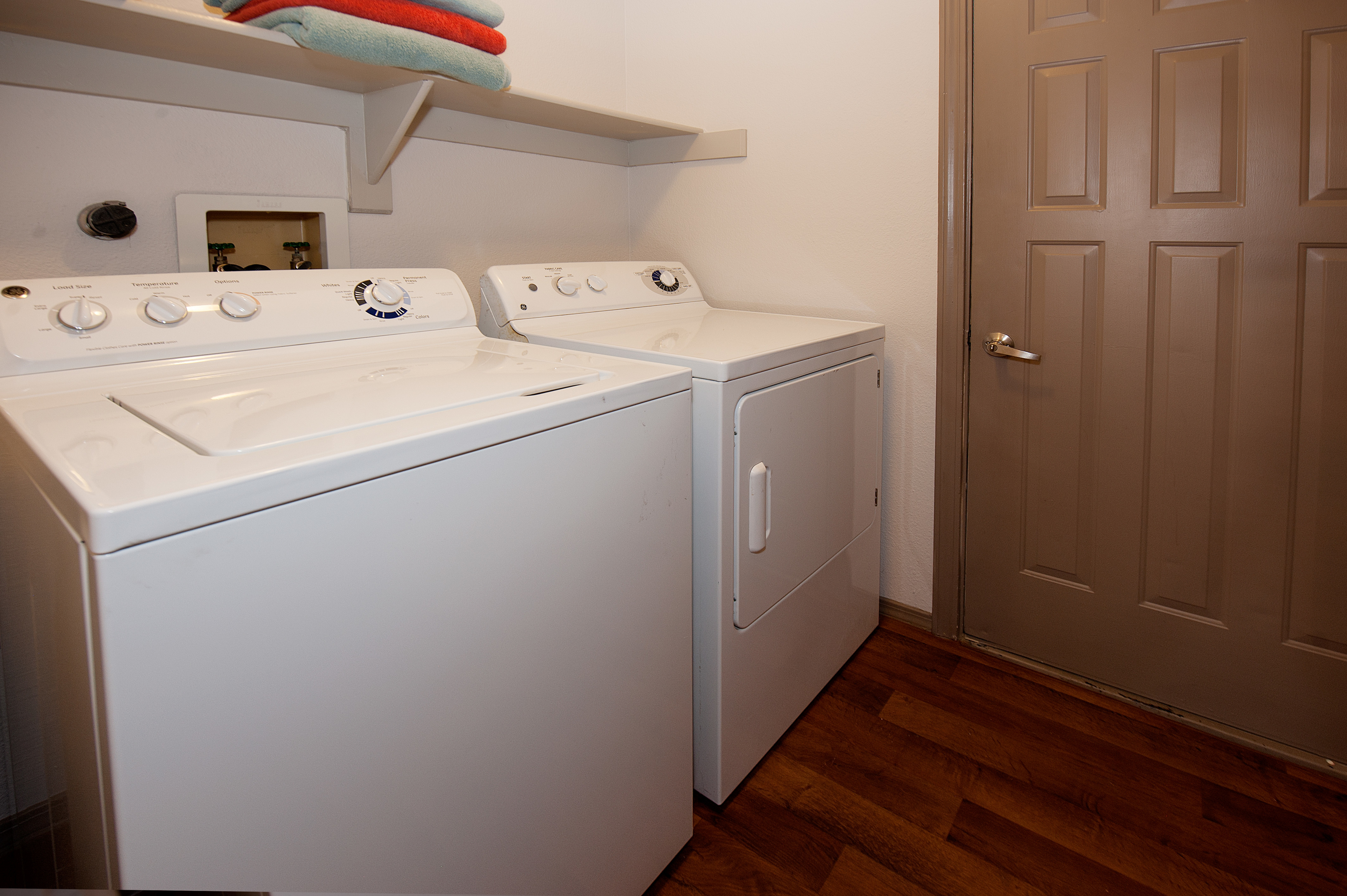 View of Laundry Room, Showing Attached, Full Size Washer and Dryer, and Shelving at Pavilions Apartments