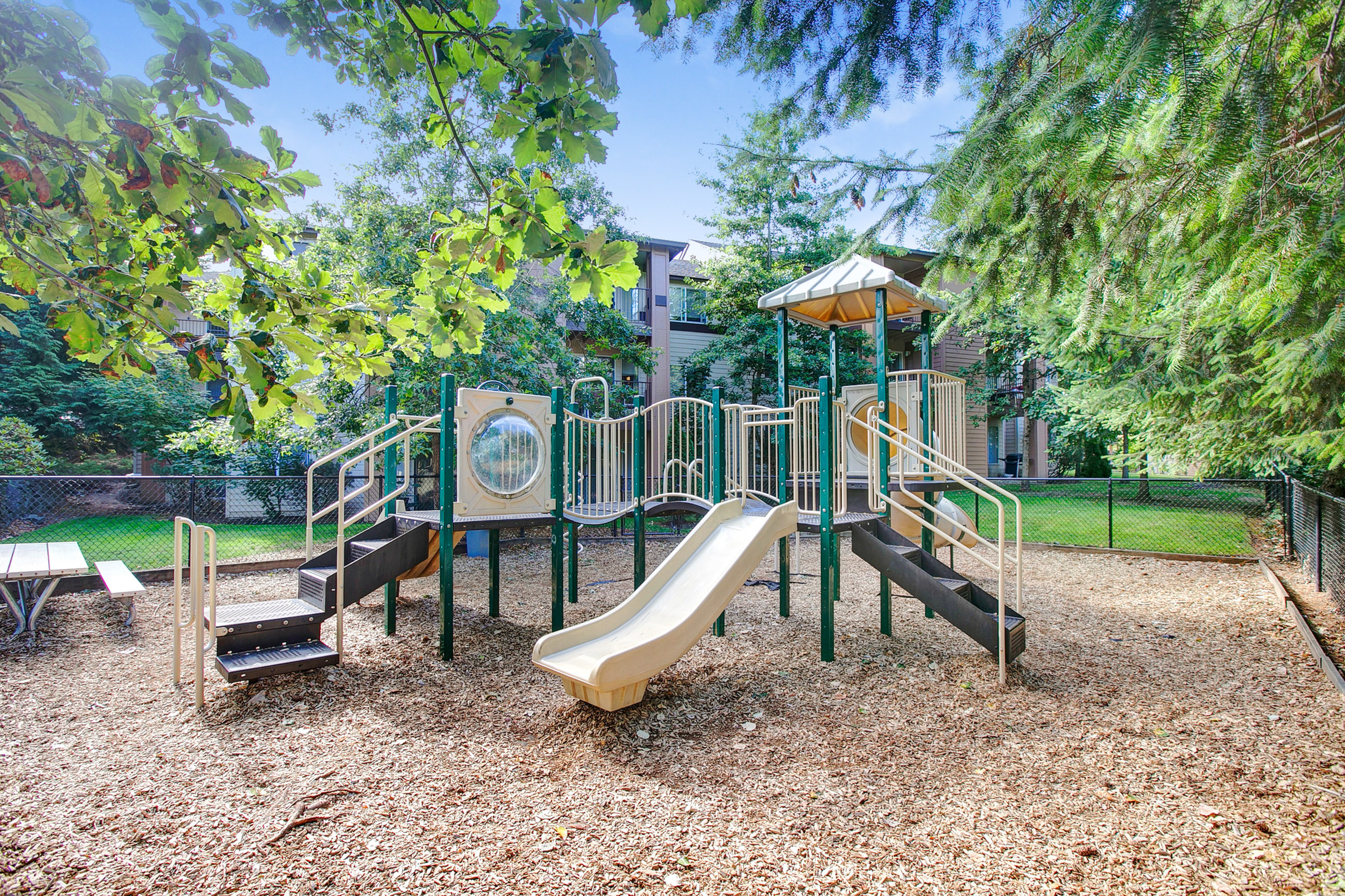 View of Fenced Playground, Showing Equipment and Landscaping at Scott Mountain Apartments