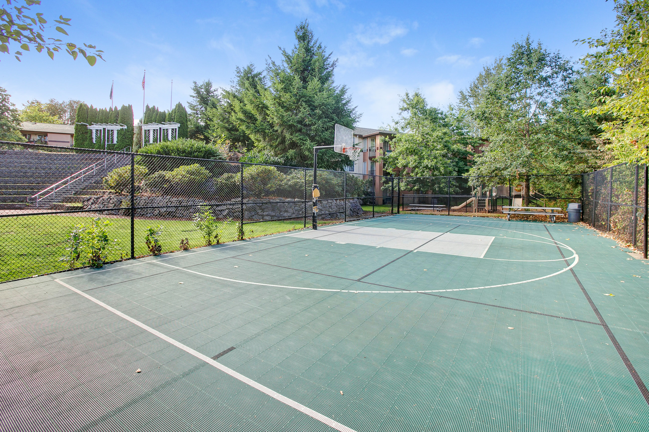 View of Sport Court, Showing Fenced Area and Basketball Net at Scott Mountain Apartments