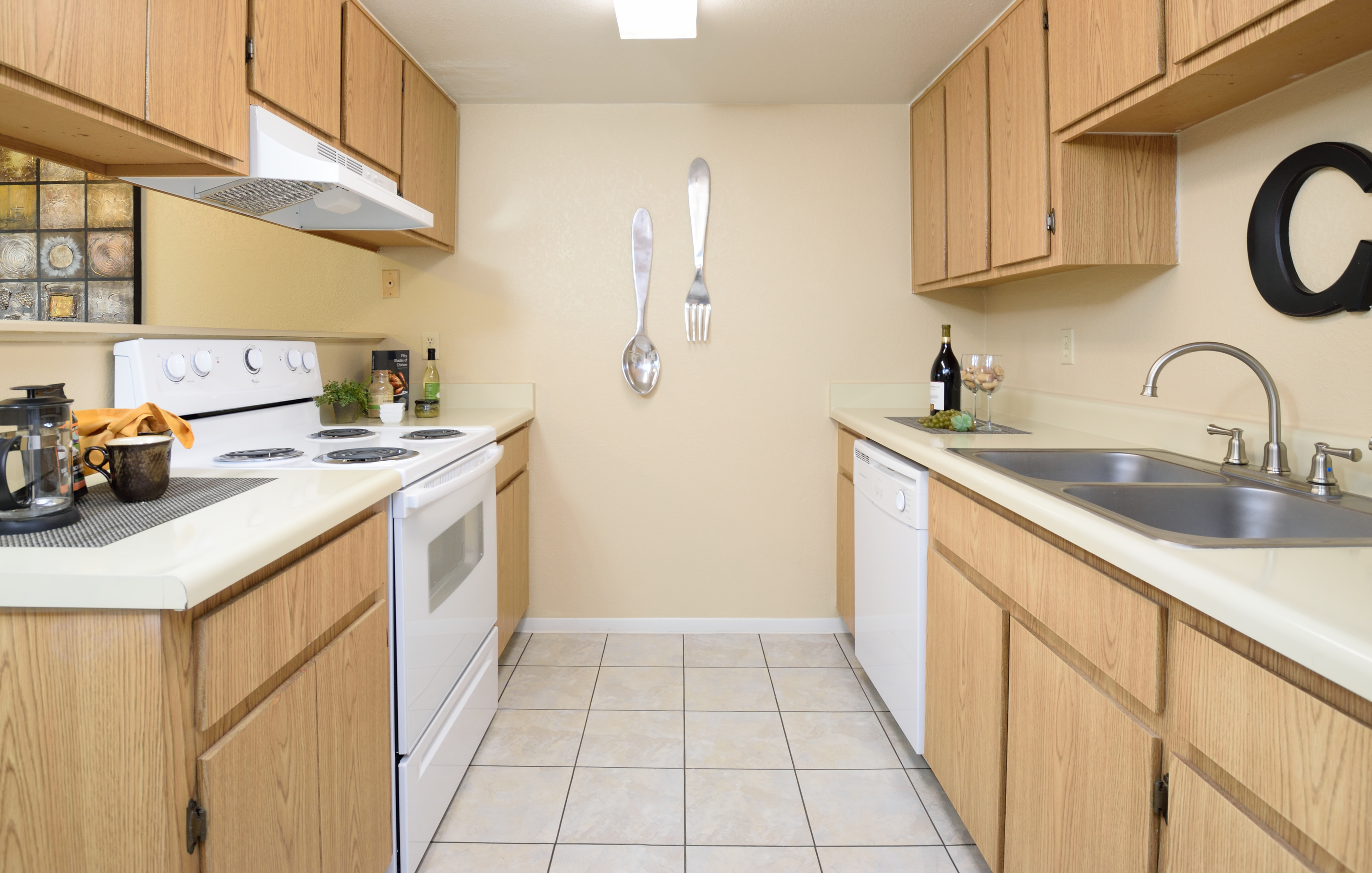 View of Kitchen, Showing Galley Style, Gas Appliances, Tile Flooring, Cabinets, Double Sink and Counter Tops,  at Camelot Apartments
