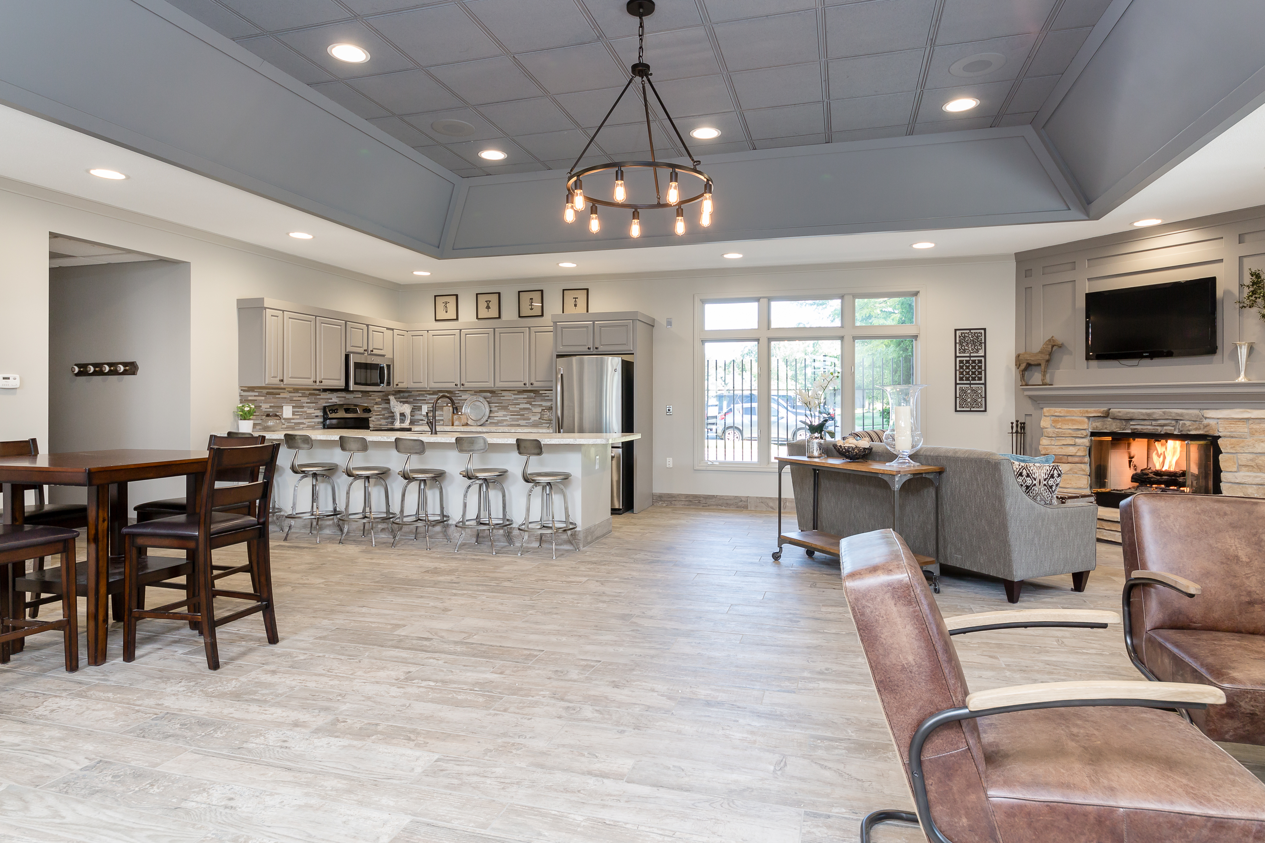 View of Clubhouse, Showing Community Kitchen, Lounge Space, Plank Flooring, Fireplace and Windows at Clearview Apartments
