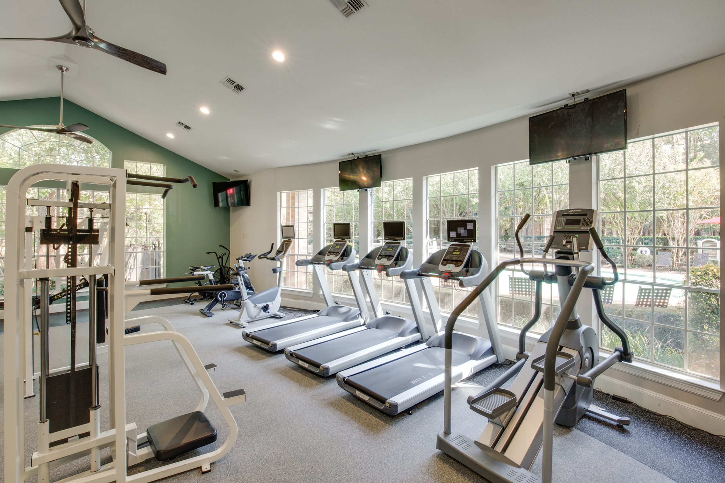 View of Fitness Center with Ceiling Fan, Cardio Machines, and Mounted Flat Screen TVs at Raveneaux Apartments