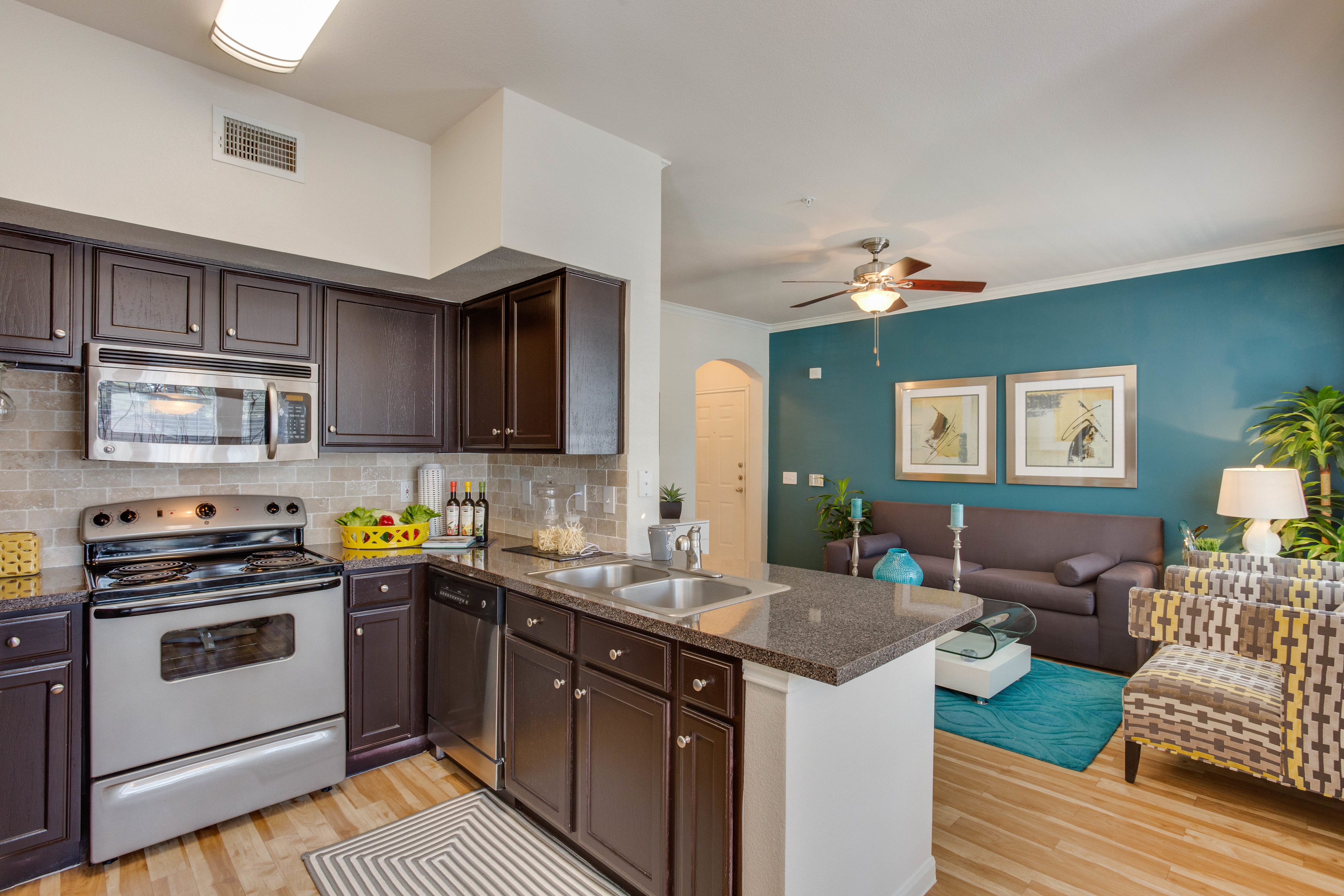 View of Kitchen with Stainless Steel Appliances, Plank-Wood Flooring, and View of Living Room at Ravneaux Apartments