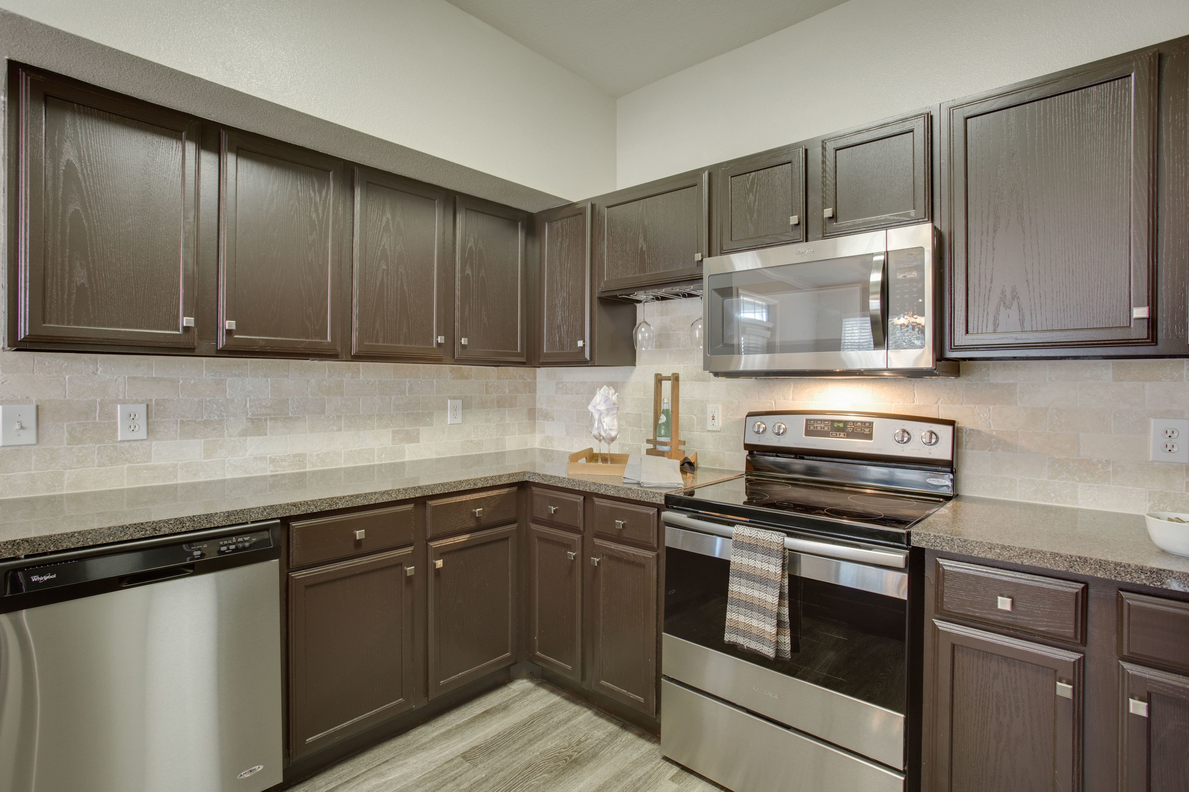 View of Kitchen with Plank-Wood Flooring and Stainless Steel Appliances and Raveneaux Apartments