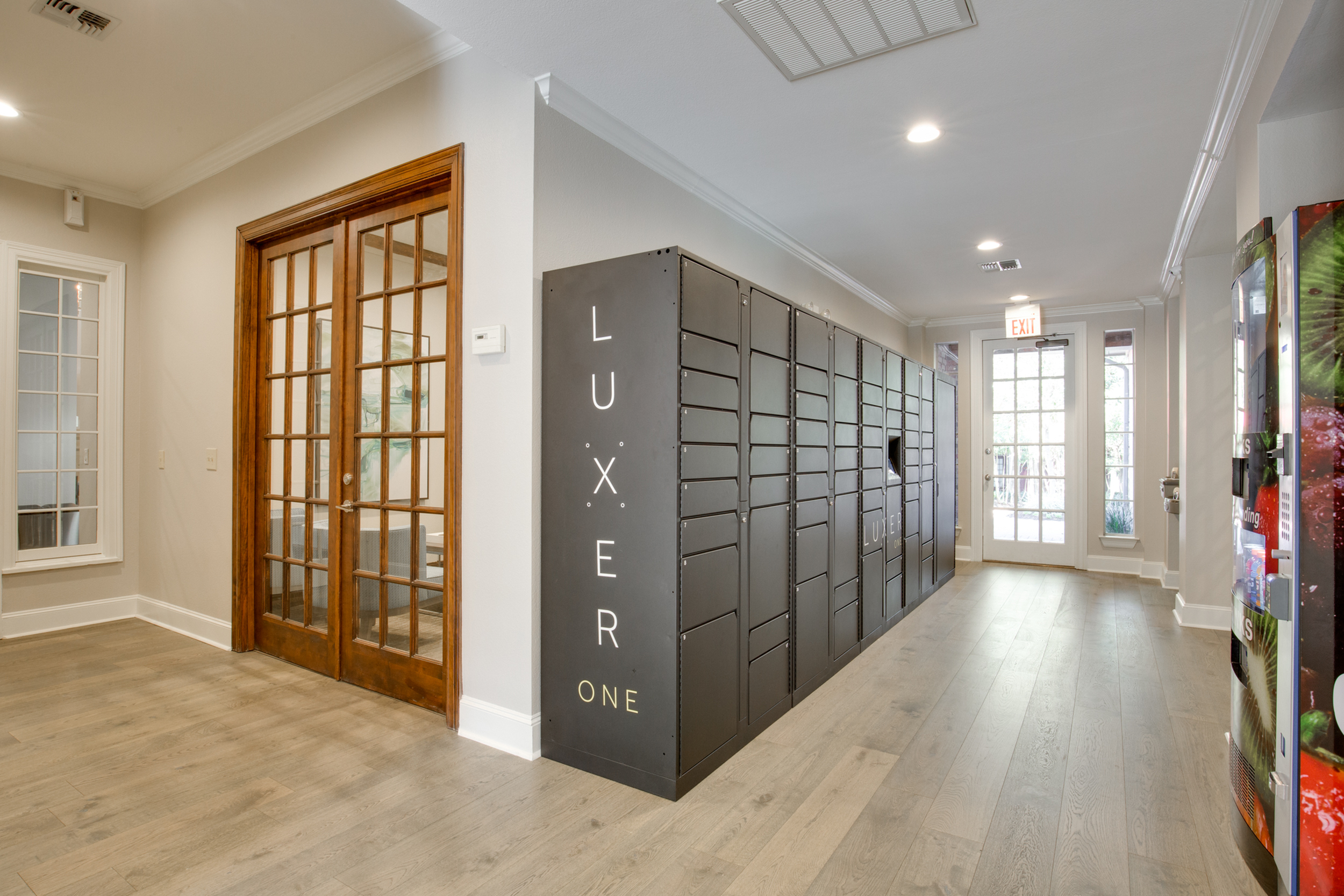 View of Luxer One Package Lockers with Wood Floors and Hallway at Raveneaux Apartments