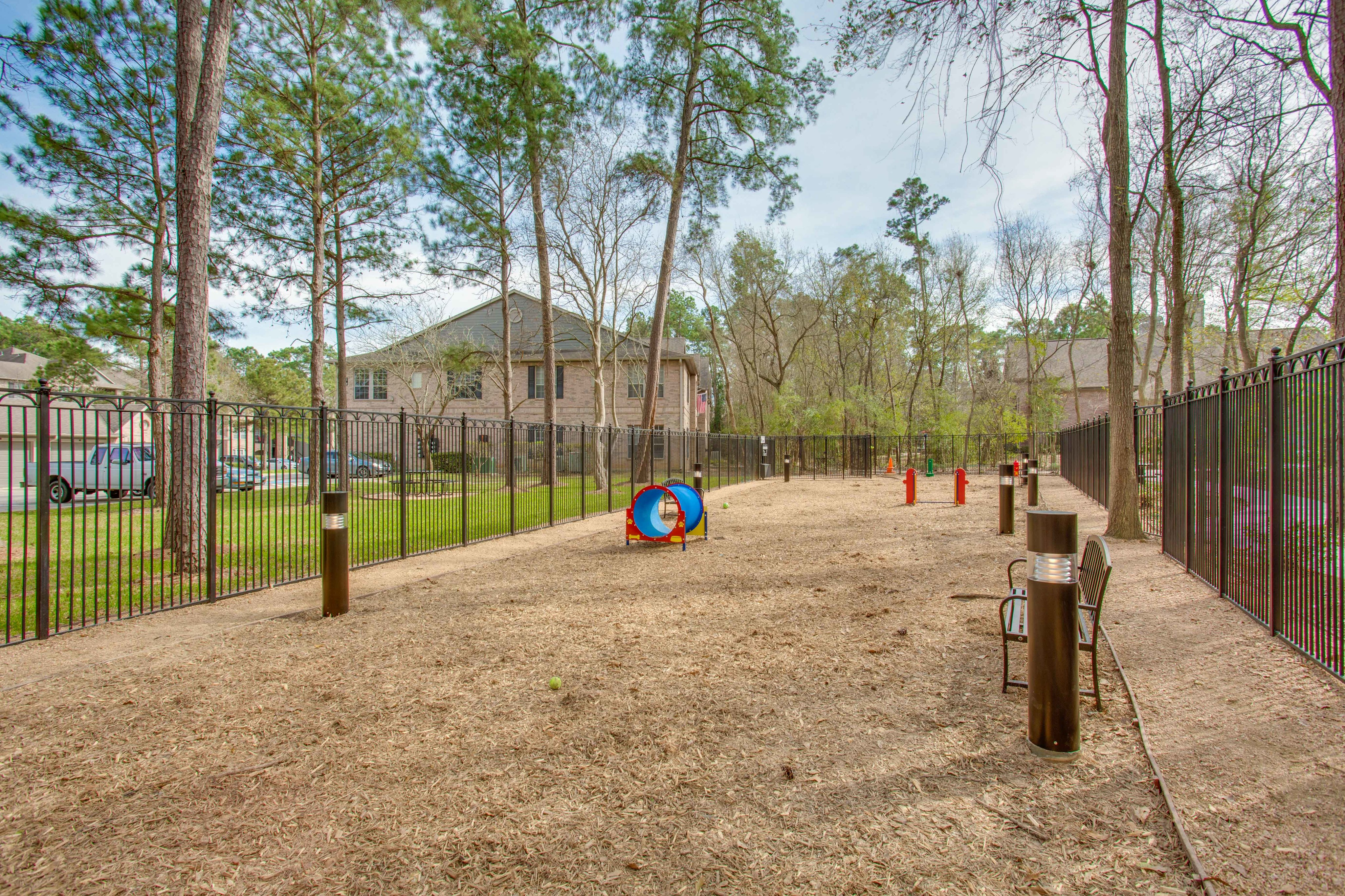 View of Fenced-In Dog Park with Agility Course and Landscaping at Raveneaux Apartments