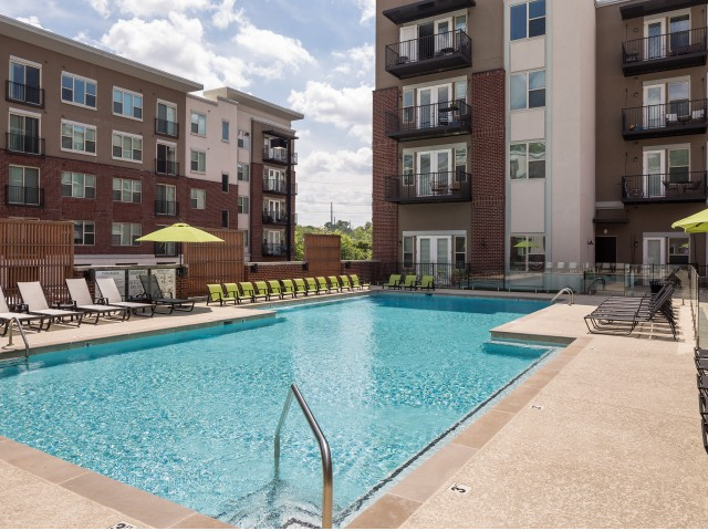 View of Pool Area, Showing Fenced-In Area, Loungers, and Apartment Buildings Surrounding at The Melrose Apartments