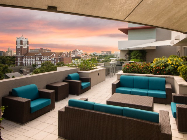 View of Rooftop Lounge, Showing Outdoor Furniture, Grilling Lounge, and View of Downtown St. Pete at Cottonwood Bayview Apartments