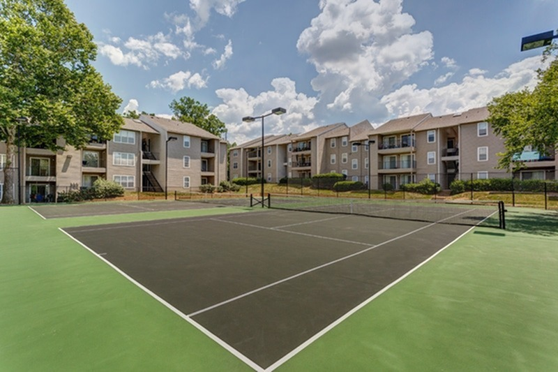 View of Tennis Courts, Showing Fenced-In Area and Apartment Buildings in Background at 1070 Main Apartments