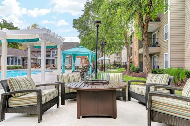 View of Pool Area, Showing Fire Pit, Pool Chairs, Cabana, and Pergola at 1070 Main Apartments
